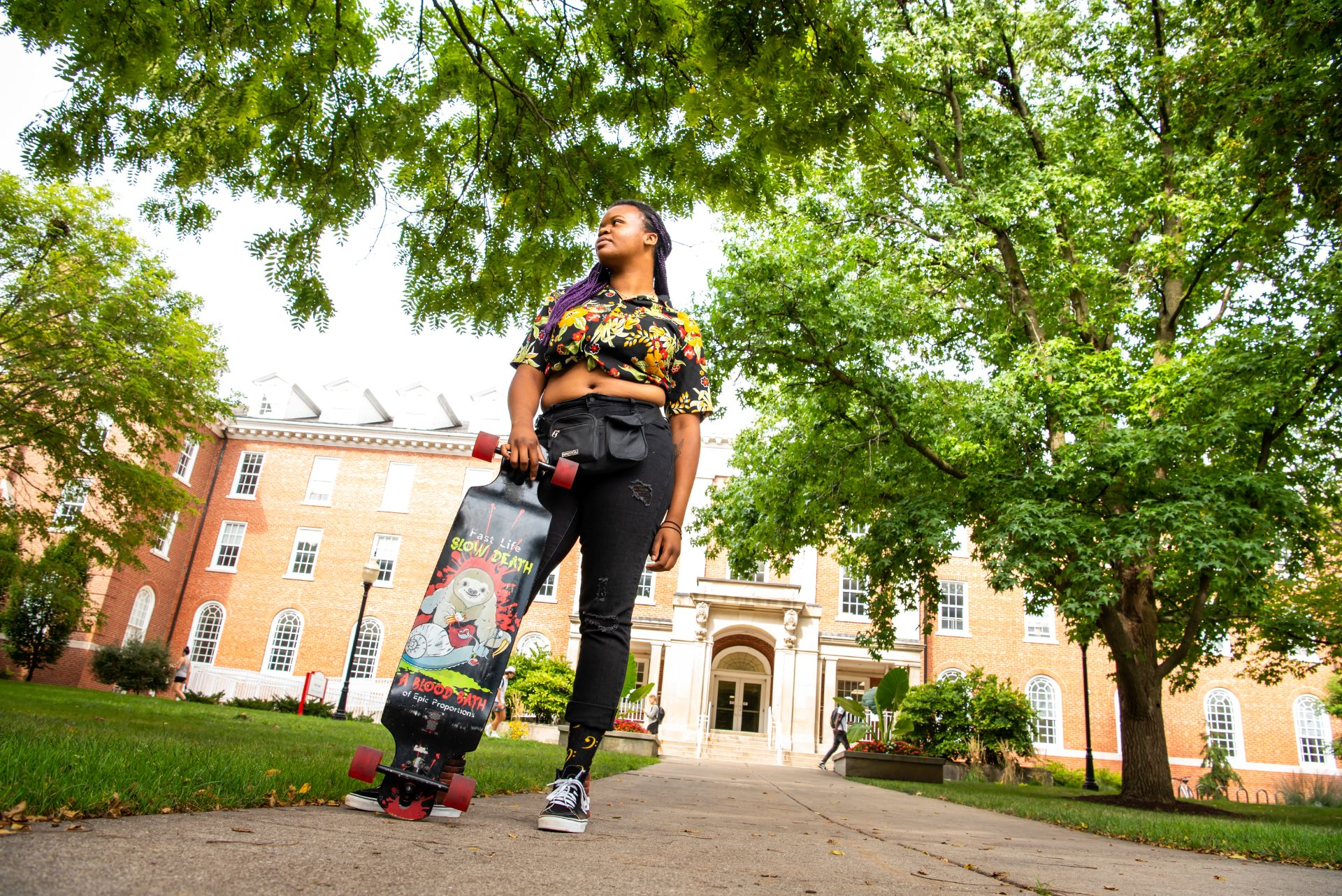 Miki McCarthy skateboards in front of Fell Hall on her way to class.
