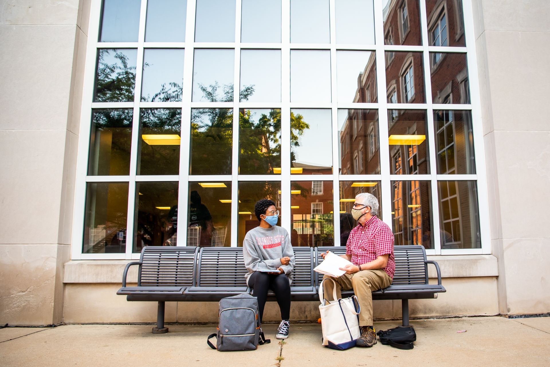 Public relations major Kyah Joseph and Music Professor Tom Faux sit outside of Schroeder Hall for a one-on-one lesson in Faux's Experiencing Music course.