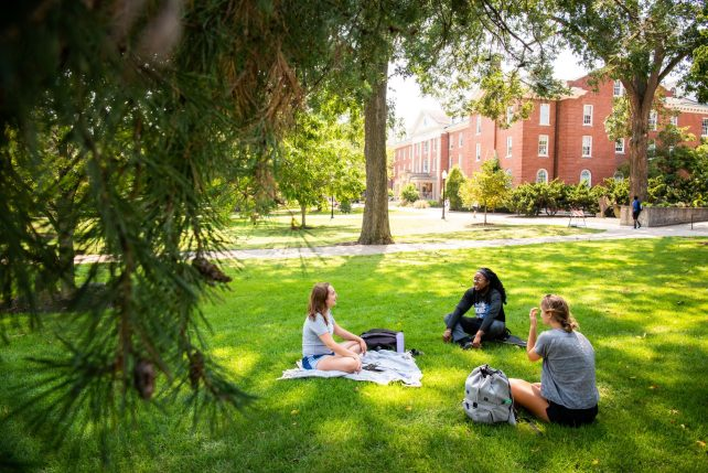 Campus ministry leader Kelsey Kamm (left), sits on the Quad with Aspen Bush (middle), and Madeline Sfura (right) to chat about opportunities within Cru at Illinois State.