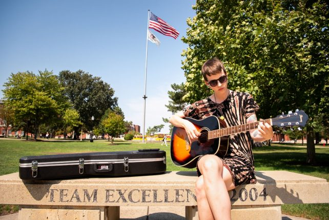"""Rachel Hooker, who is a first-year graduate student studying music therapy, serenades the Quad with her musical talents by singing """"What Ever Happened?"""" by The Strokes."""