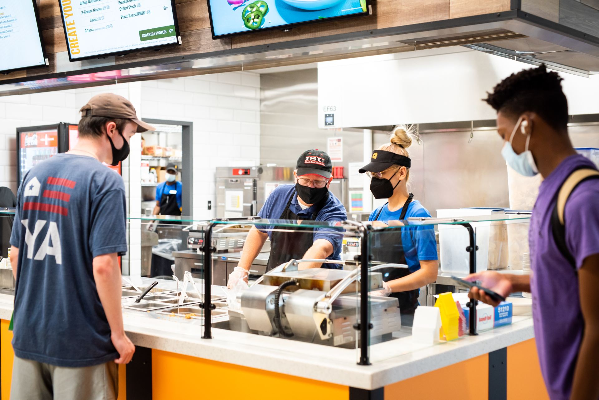 Event Management, Dining, and Hospitality Director Bill Legett assists MBA graduate student Meichen Fu during her first day working at Qdoba in the Bone Student Center.