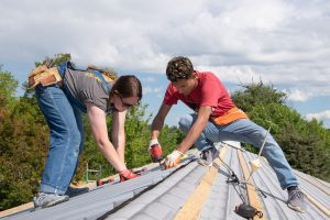 Two students working on a roof
