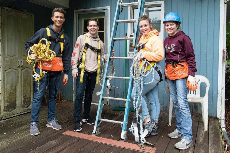 Four students posed by a ladder