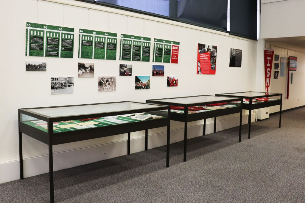 Photograph of display cases and wall mounted items that make up the Coming Home exhibit at Milner Library