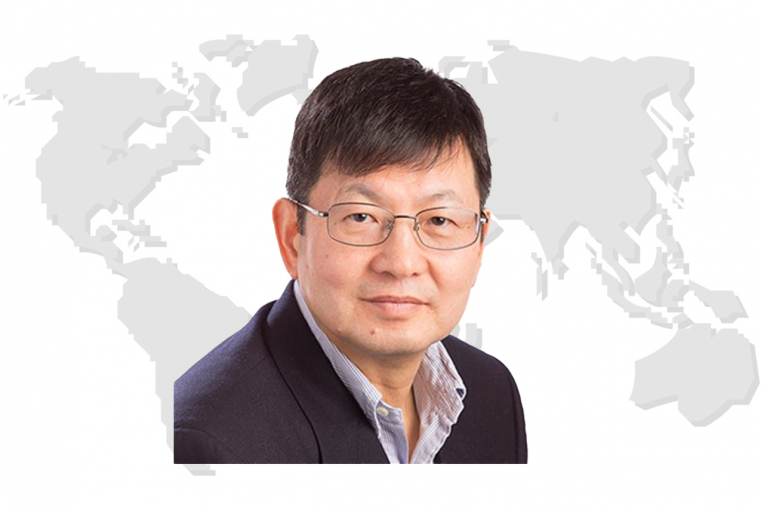 Dr. Uk Heo's image with a world map in the background