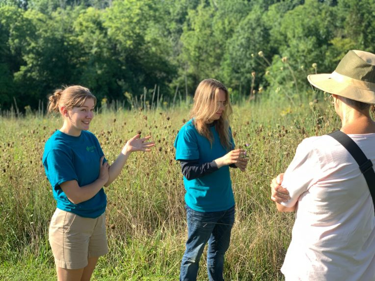 Allison Morgan, left, leads guided tours through the gardens' pollinator meadow at Yew Dell Botanical Gardens.