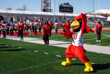 Reggie Redbird on the football field in front of color guard members