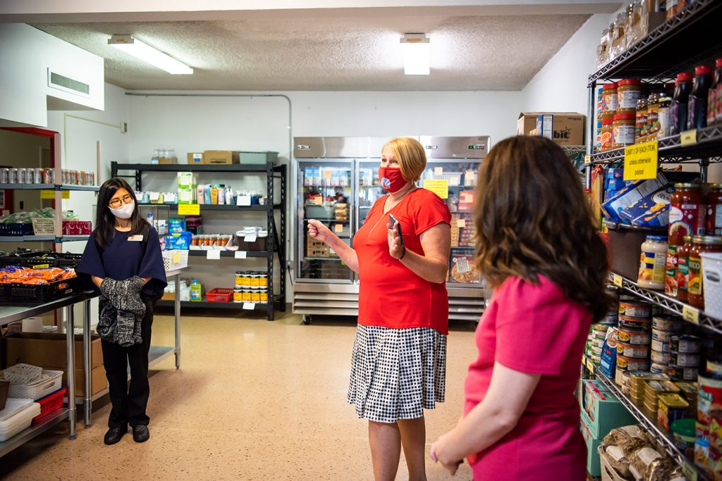 Three individuals in a food pantry surrounded by shelves containing food items