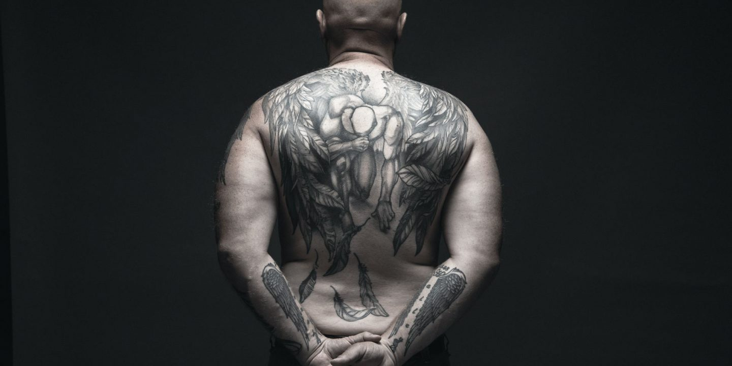 Cover image of Redbird Scholar's fall 2021 issue showing man's back and lower arms covered with tattoos