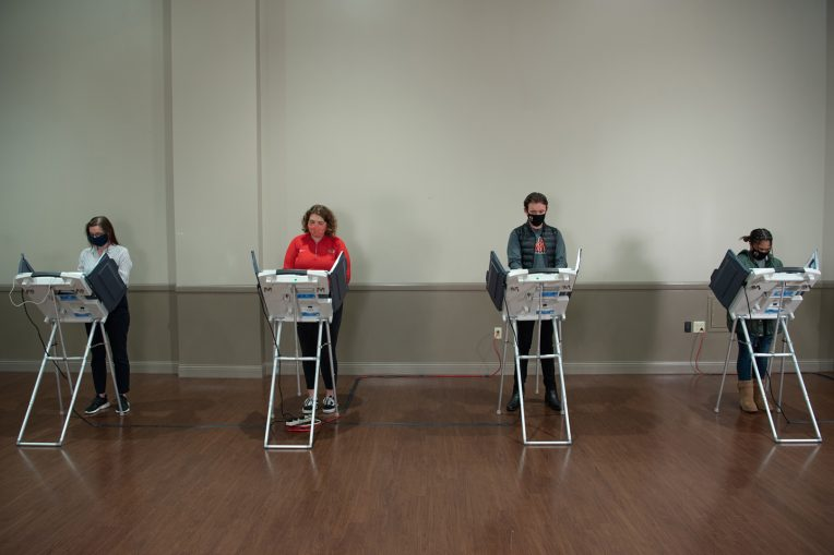 four individuals at voting machines