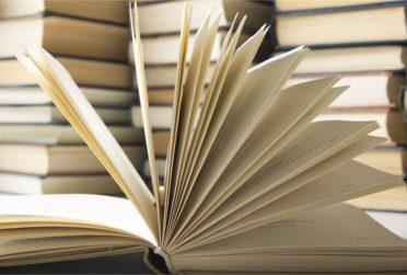 Open book, hardback books on wooden table.
