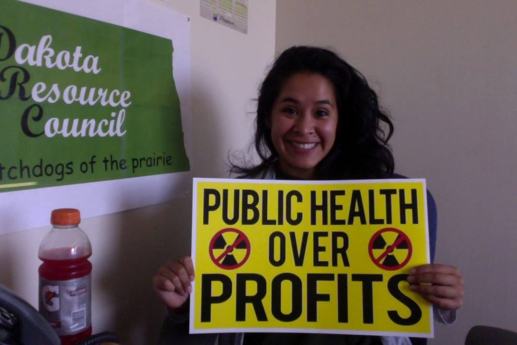 """Stevenson Center alum Cecilia Montesdeoca holding up a small yellow sign that says """"Public Health Over Profits"""""""