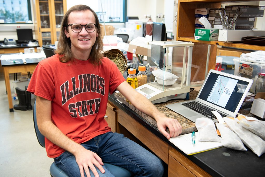Portrait of Alex Hafner next to his research in a lab.