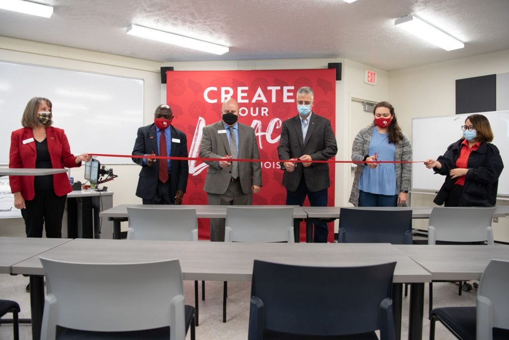 People cutting a ribbon at a grand opening.