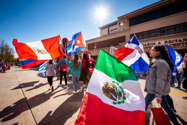 Students waving flags at a parade.