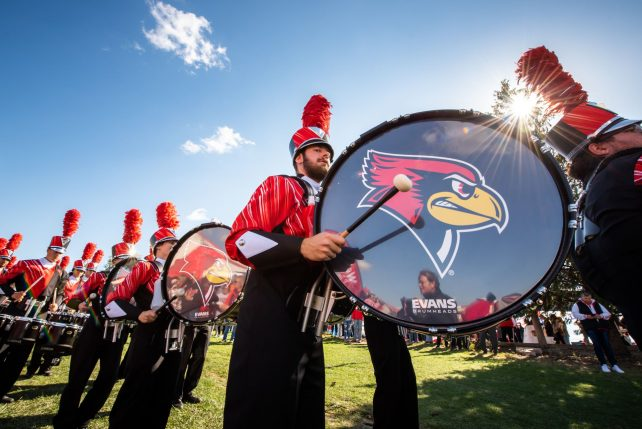 Photo of a band student performing at a Homecoming game.