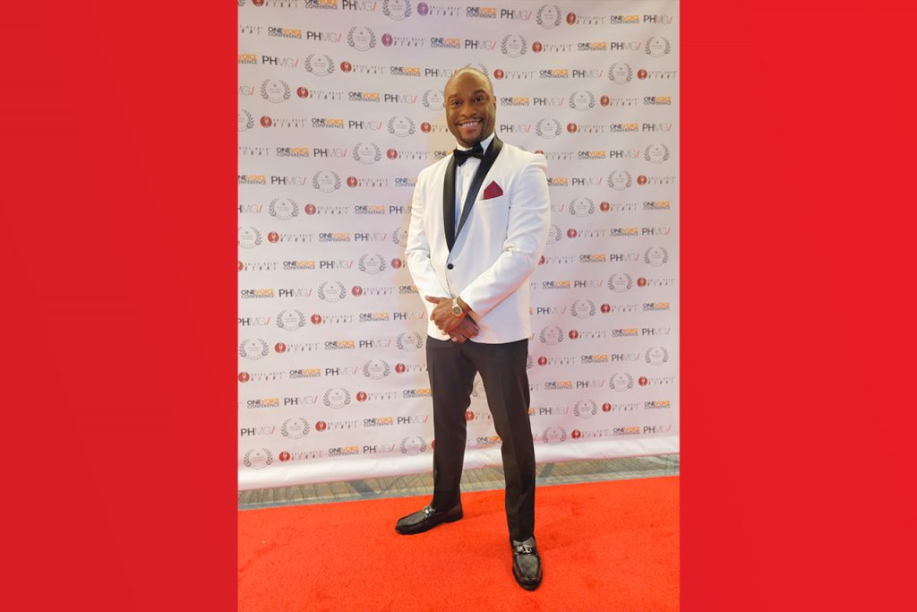 Man in tuxedo on posing on the red carpet at an awards show.