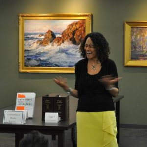 Dean Richardson gesturing and smiling during her talk at the 2017 event with books in the background.