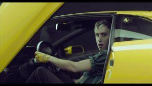 Bilderbuch lead singer in a yellow sportscar