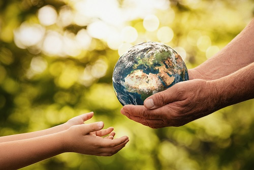 Close up of senior hands giving small planet earth to a child over defocused green background with copy space