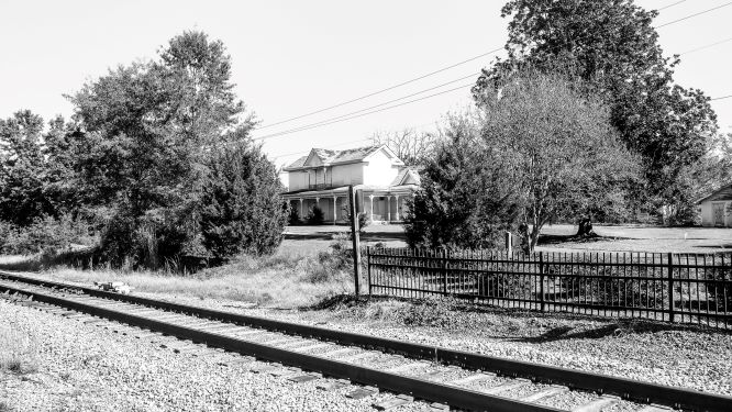 BW Photo of a railroad with house in background