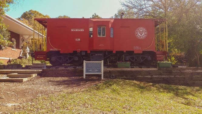 Red train caboose with sign in front. Grass in foreground blue sky in back.