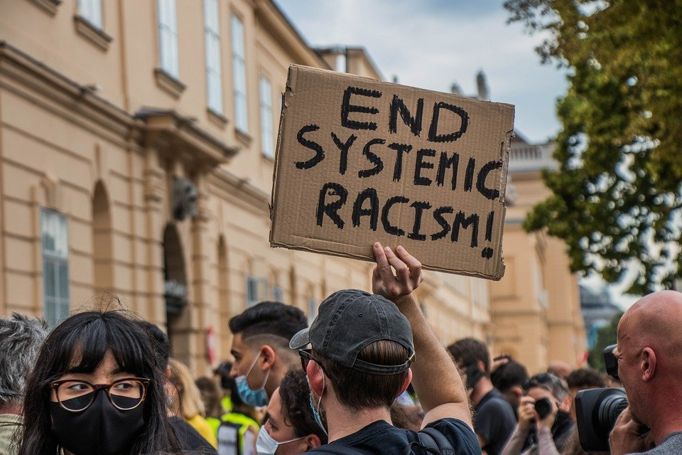 """image of a crowded protest, with a sign reading """"End systemic racism."""""""