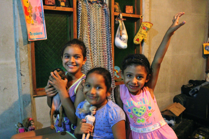 Priscilla, Rosita, and Jimena pose for a photo with their dolls and Roxy, the family's puppy