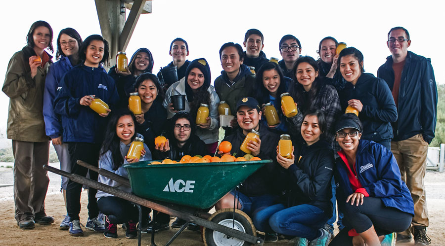 Group photo of Costa Rica Program participants holding jars of homemade orange juice