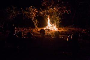 Photo of participants reflecting near an inviting bonfire.