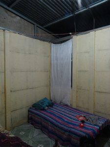 Photo depicting bedroom with gap between interior wall and roof.