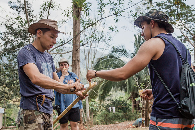 Marcos cuts a piece of sugar cane off for daring participant Danny.