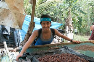 The author poses with drying cacao beans.