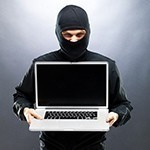 a man in a black mask holds a laptop menacingly