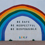 A painted wall with a rainbow and be safe, be respectful, be responsible motivational words