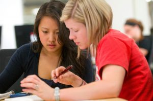 Two young women sit at a table and look intently at a document. It is clear they are working together.