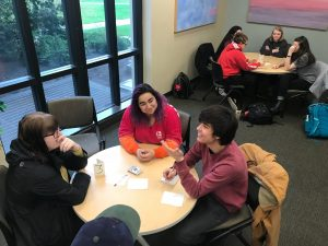 students and tutors sitting together at a small round table
