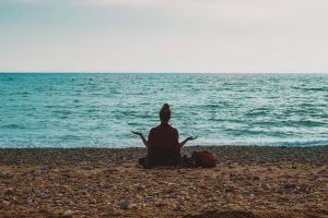 person meditating on a beach