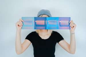 woman holding blue paper over her face