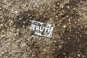 Small sign saying truth on pavement