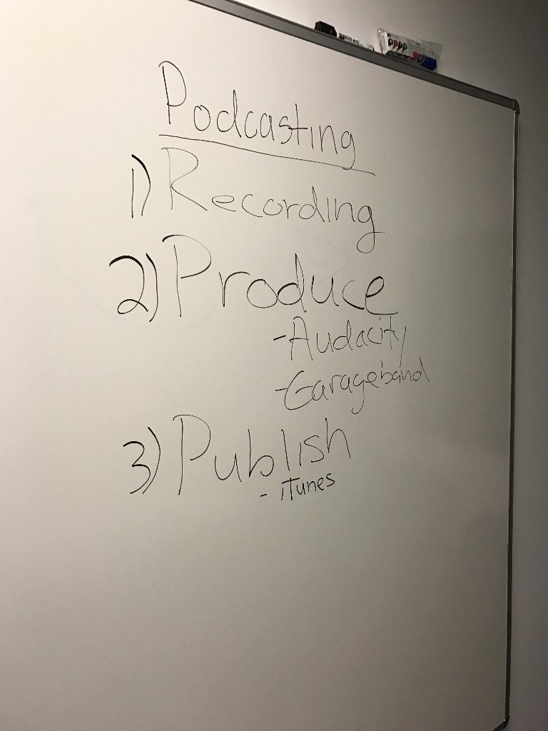 "a whiteboard with text written in black marker. we are viewing from an off angle. the text readings ""Podcasting: 1) Recordings, 2) Produce - Audacity - Garageband, 3) Publish - iTunes"