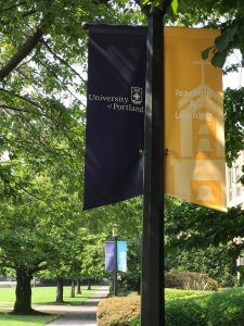Photo of the University of Portland courtyard path with two flags, UP & Teaching and Learning.