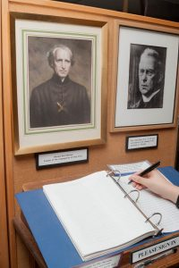 Guest signing the register below a picture of Blessed Basil Moreau, C.S.C.