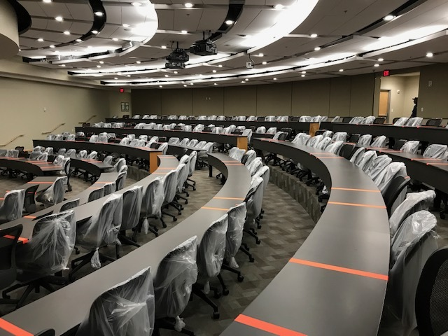 Tape and covered chairs indicate which seats and portions of a table are unavailable to students in a socially distanced lecture hall.