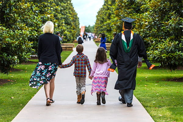 MBA graduate in cap and gown with family on the UT Dallas campus