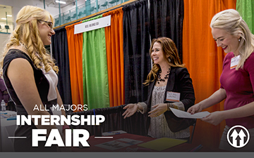 A student speaking with two recruiters at a career fair