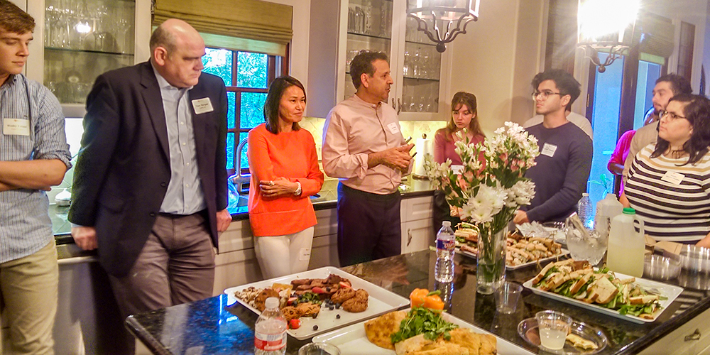 Hosts Kal Malik BS'86 (fourth from left) and his wife, Feli Wong (third from left), welcome the incoming students and their families to the Houston send-off.