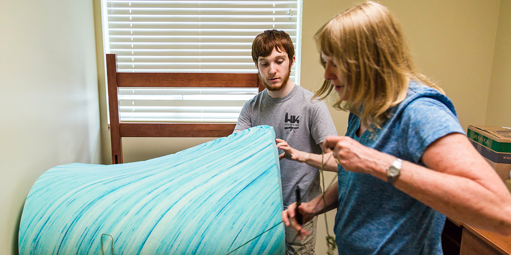 Arts and technology freshman Brett Austin receives help from his mother as he unpacks his room.