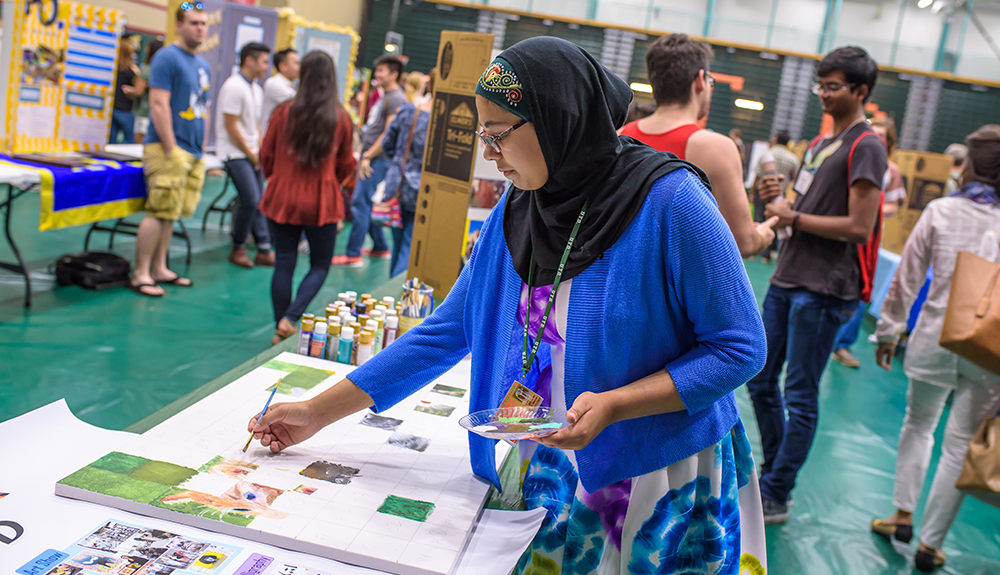 Khadijah Mazhar of Art UTD invited attendees to paint individual squares for a collaborative art piece.