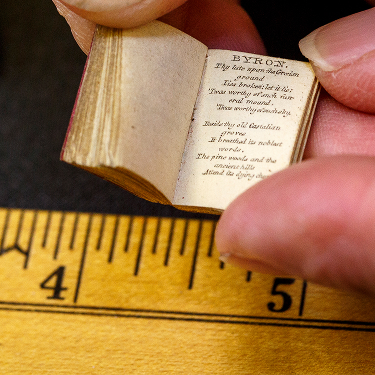 Small book opened to a page of Lord Byron being held over ruler